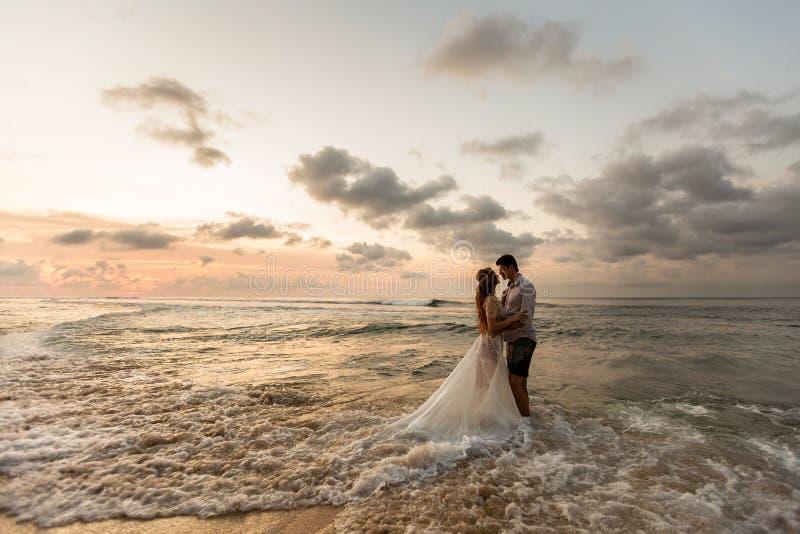 海滩的新婚佳偶在日落 库存照片