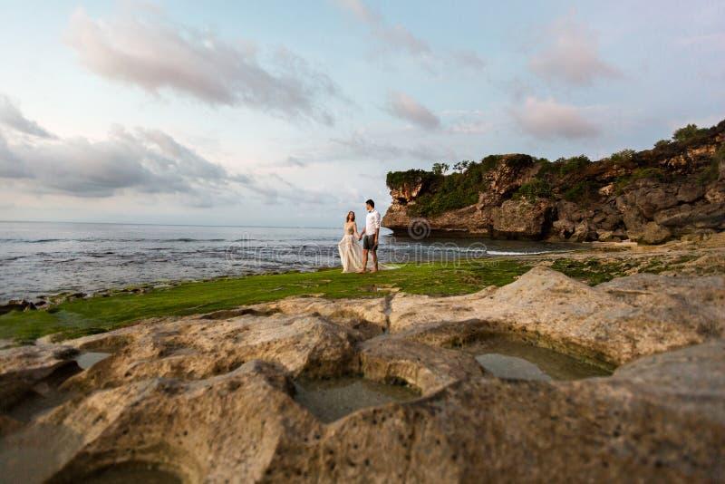 海滩的新婚佳偶在日落 免版税库存照片