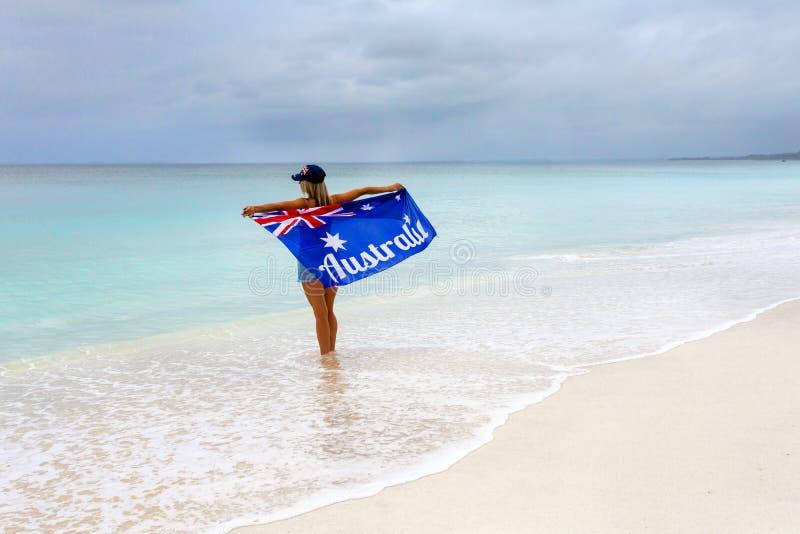 海滩的爱国的澳大利亚妇女与旗子 免版税库存照片