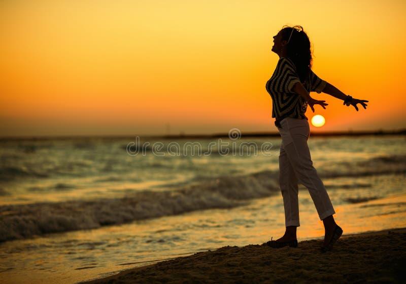海滩的现代妇女在日落欣喜 免版税库存照片