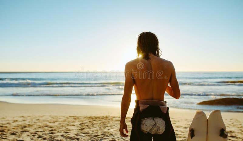 海滩的男性冲浪者与水橇板 免版税库存照片