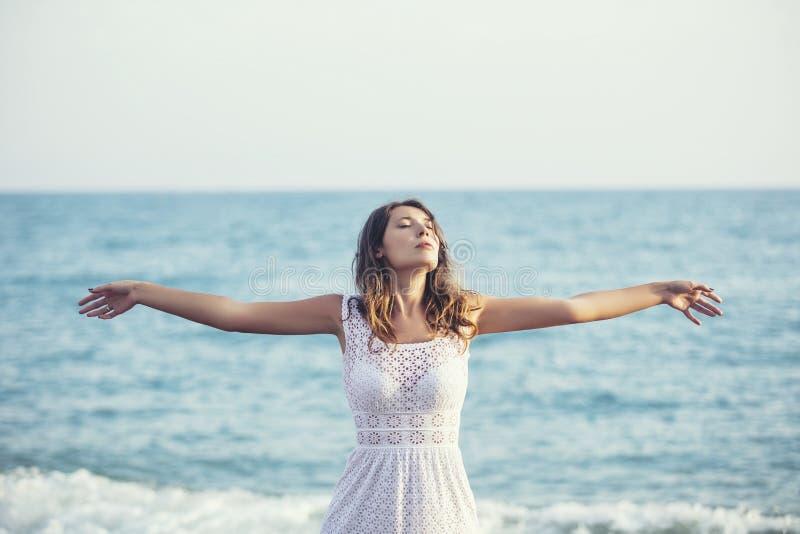 海滩的美丽的妇女在愉快一件白色的礼服 免版税库存图片