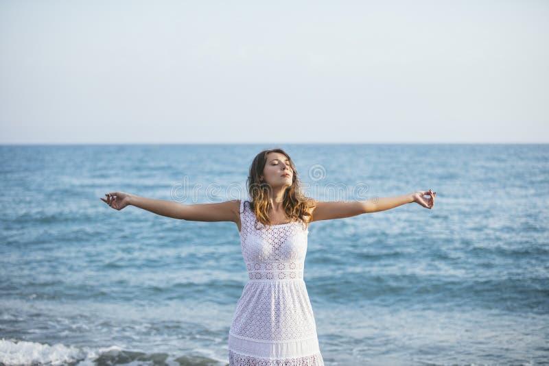 海滩的美丽的妇女在愉快一件白色的礼服 免版税库存照片