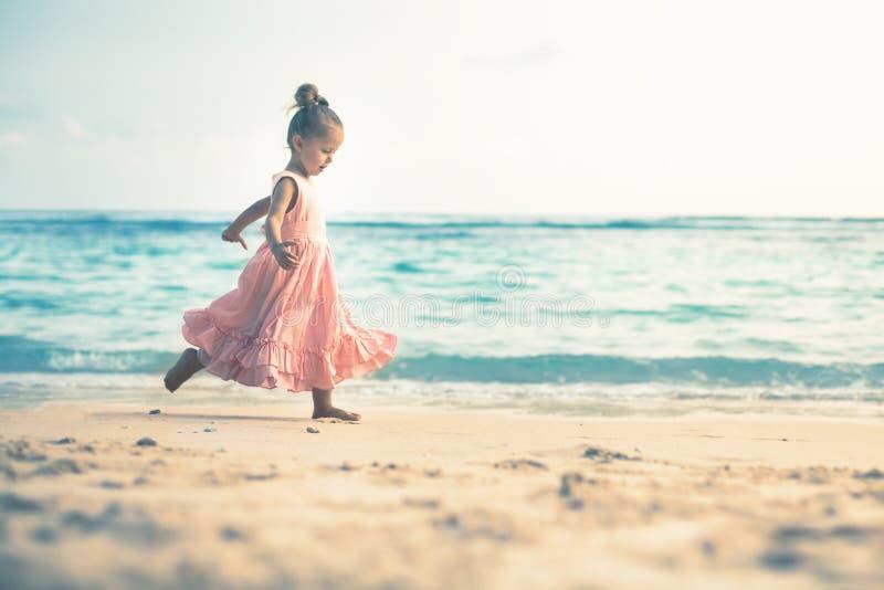 海滩的美丽的小女孩 孩子的Sunblock奶油 库存图片