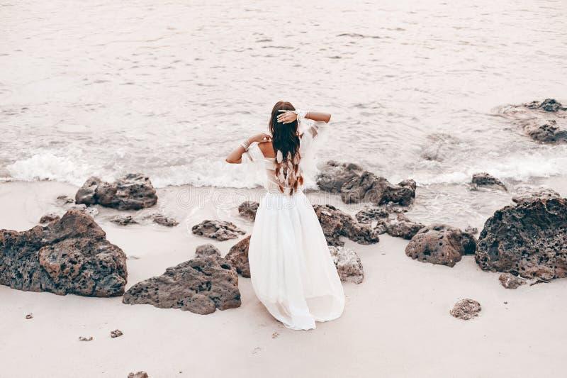 海滩的美丽的年轻时髦的boho妇女在日落 免版税库存图片