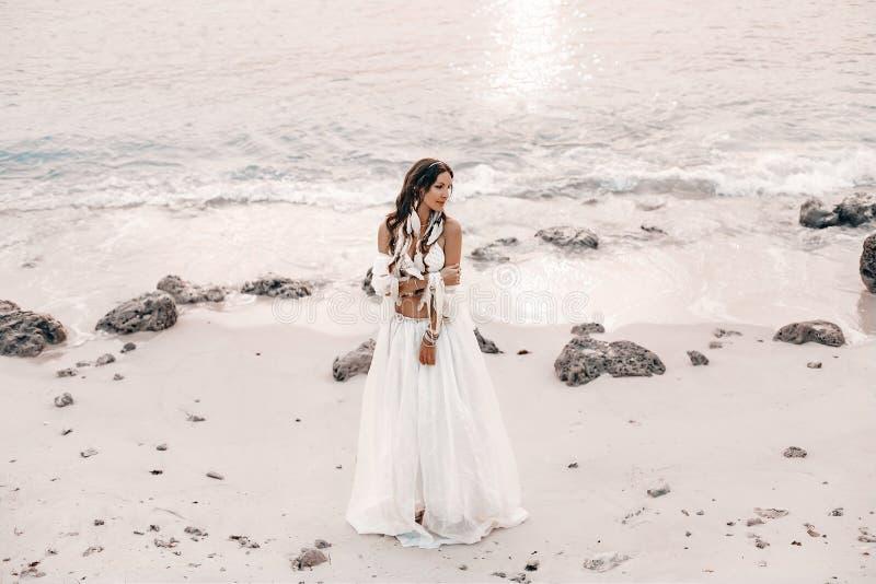 海滩的美丽的年轻时髦的boho妇女在日落 库存照片