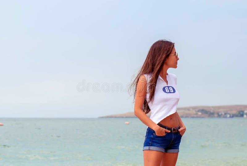 海滩的美丽的运动女孩啦啦队员与长的头发和在牛仔布短裤 库存照片
