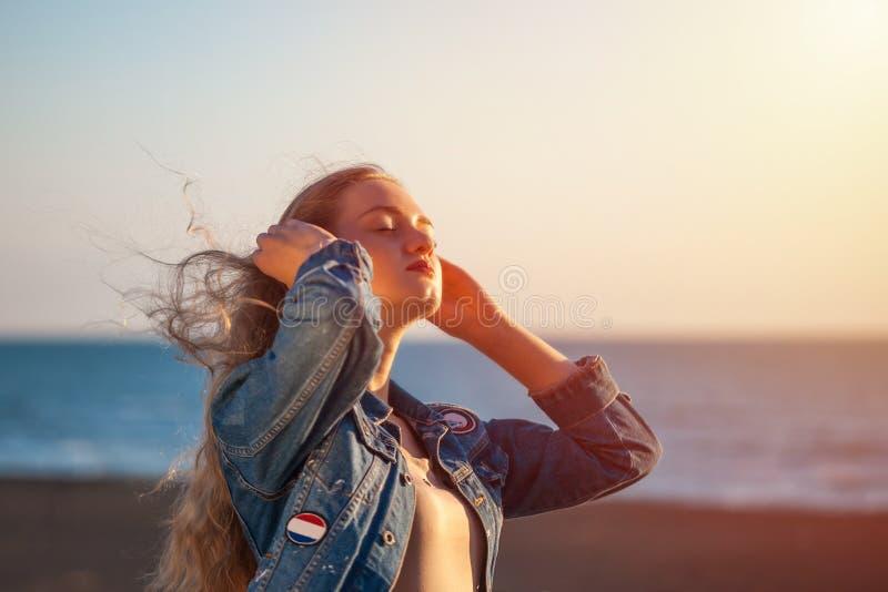 海滩的美女享受在sunse的新鲜空气自由 免版税库存照片