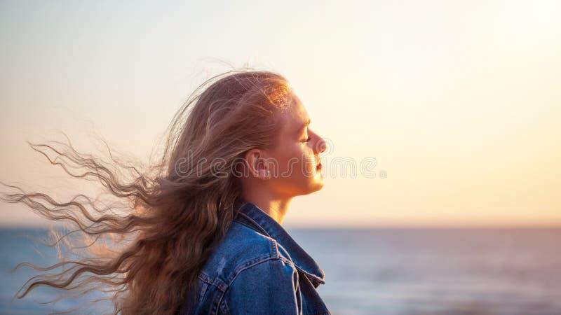 海滩的美女享受在sunse的新鲜空气自由 图库摄影
