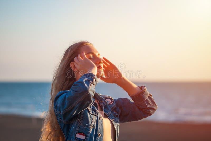 海滩的美女享受在sunse的新鲜空气自由 免版税库存图片