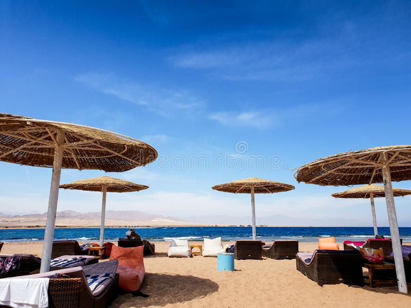 海滩的美好的图象与懒人、太阳床和装豆子小布袋的在海海滩的秸杆伞下反对天空蔚蓝 免版税库存图片