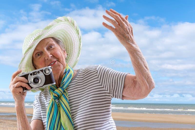 海滩的资深妇女与老葡萄酒照相机背景的海 图库摄影