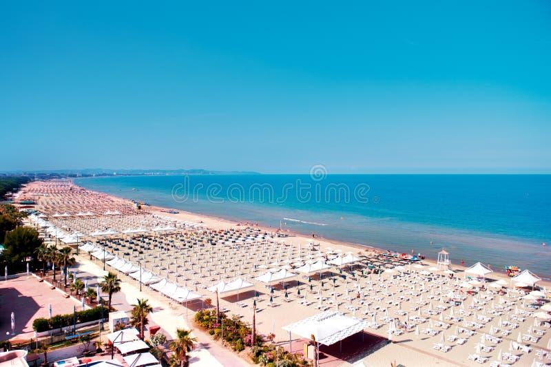 海滩的鸟瞰图都拉斯,阿尔巴尼亚,充分伞和人在夏天 免版税图库摄影
