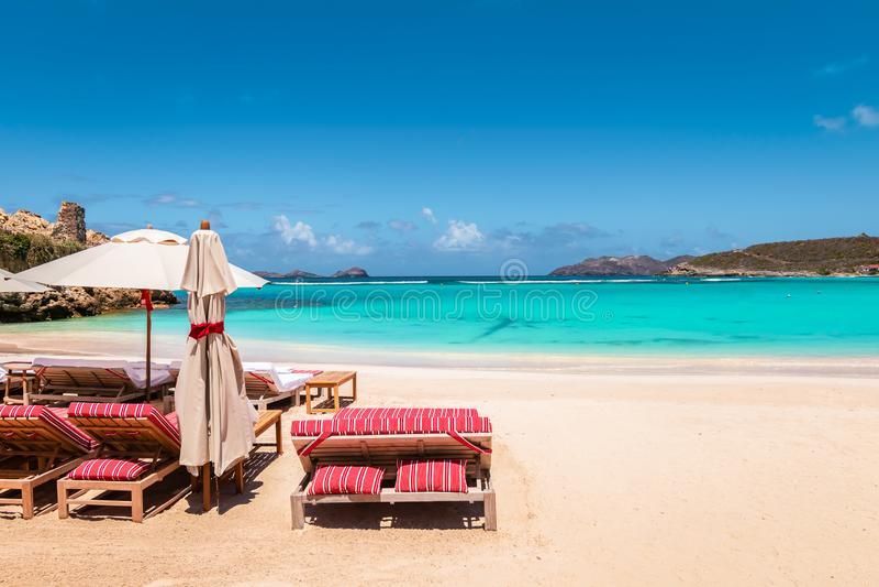 海滩睡椅和伞在热带海滩 暑假和放松背景 库存图片
