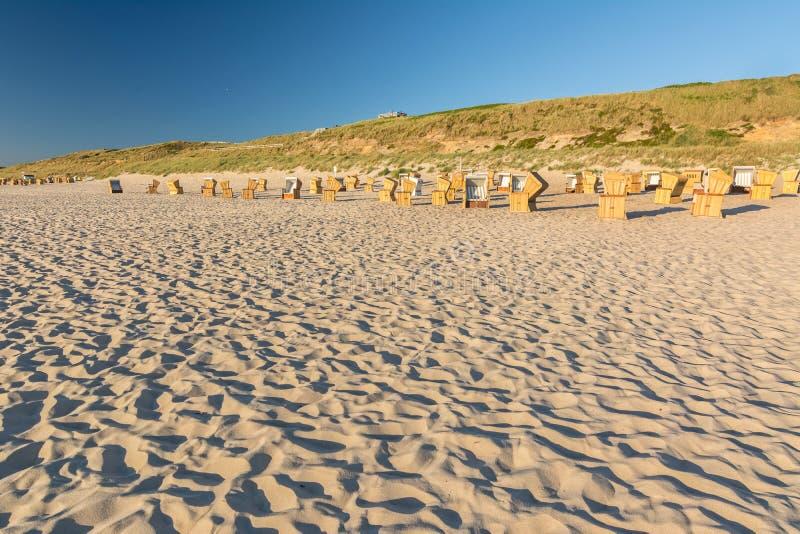 海滩睡椅和沙丘在平衡的光在美好的日落期间在西尔特 库存图片