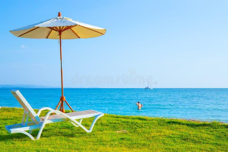 海滩睡椅和沙滩伞在草坪在海滩 海视图和明亮的天空 库存照片
