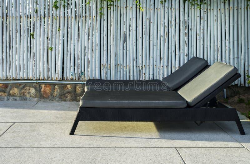 海滩睡椅旁边游泳池和日落 免版税库存图片