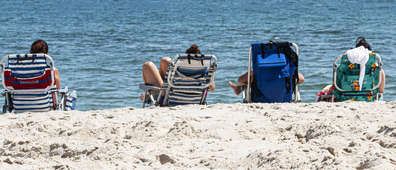 海滩睡椅的四个朋友由海洋 免版税库存图片
