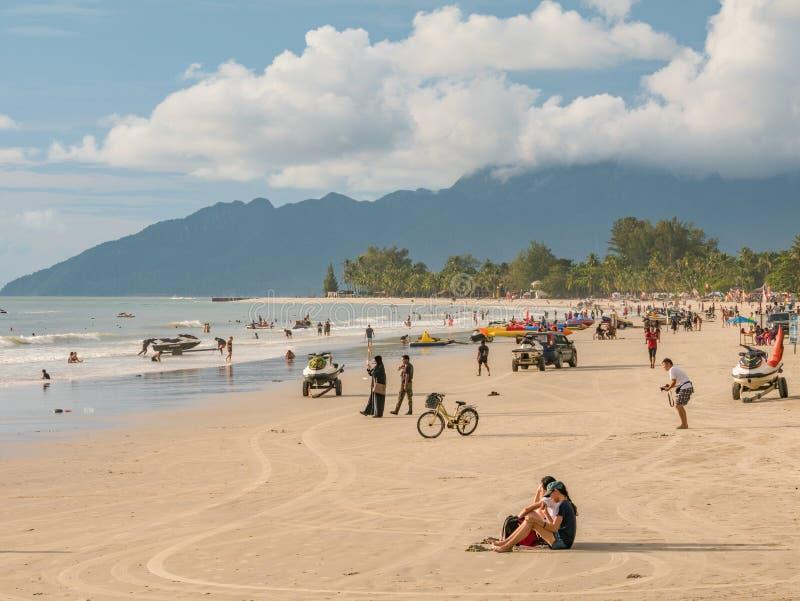 海滩等待的日落的人们在Cenang海滩,凌家卫岛 库存照片