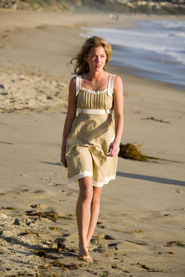 海滩美丽的女孩走的年轻人 免版税库存图片