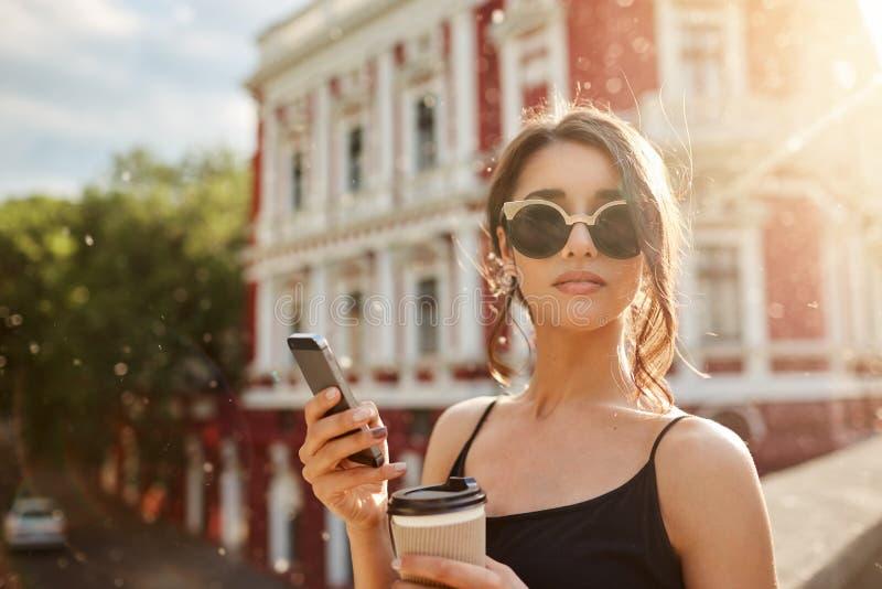 海滩美丽的日夏天妇女年轻人 关闭可爱的皮包骨头的女性白种人妇女画象有黑发的在棕褐色玻璃和黑色 免版税库存照片