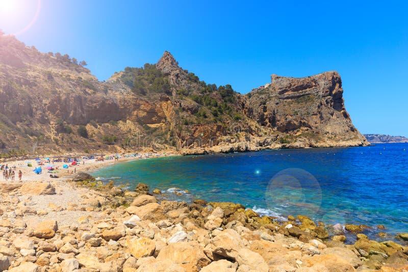 海滩美丽的景色在一个海湾的用在阳光下绿松石水, La playa Moraig在昆布雷del Sol,西班牙 免版税库存照片
