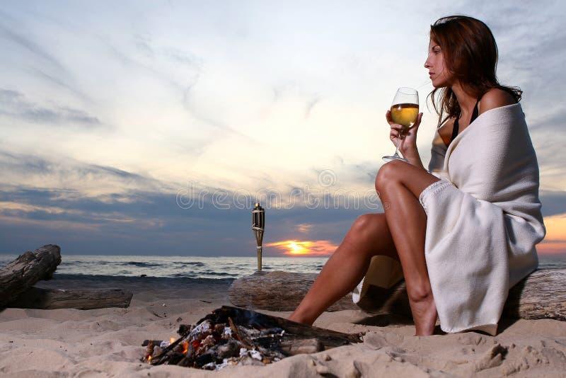 海滩美丽的饮用的酒妇女年轻人 免版税库存照片