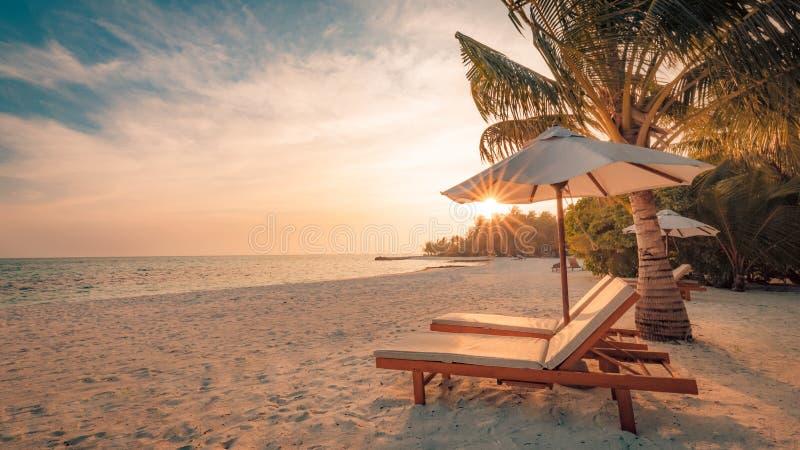 海滩美好的日落 在沙滩的椅子在海附近 暑假和假期概念 激动人心的热带场面 库存照片