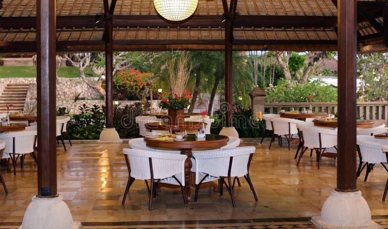 海滩胜地的优等的典雅和现代餐馆在巴厘岛印度尼西亚 位子、桌和灯在豪华优质旅馆 免版税库存照片