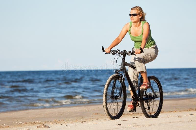 海滩自行车骑马妇女 库存照片
