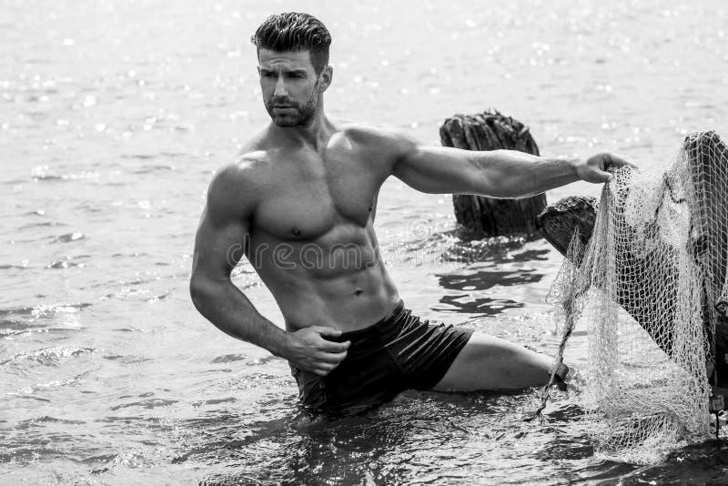 海滩英俊的人 库存图片