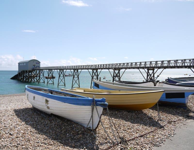 海滩蓝色小船小卵石selsey黄色 库存图片