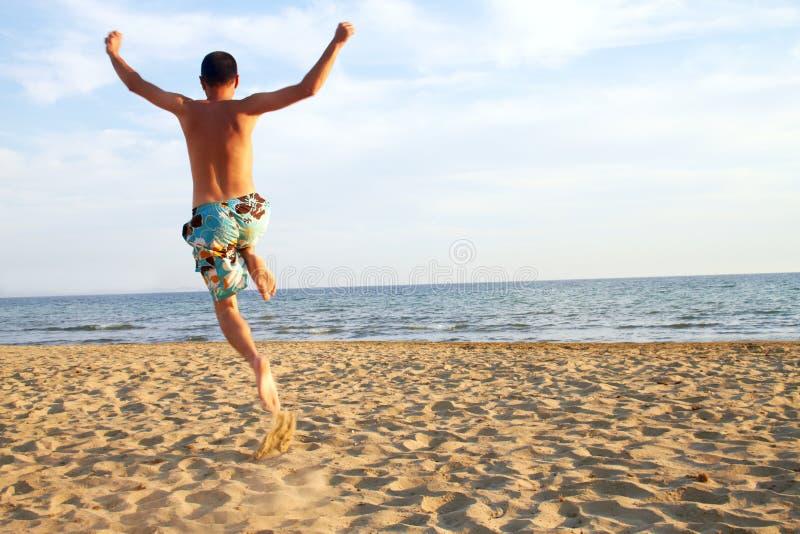 海滩跳的人年轻人 库存图片