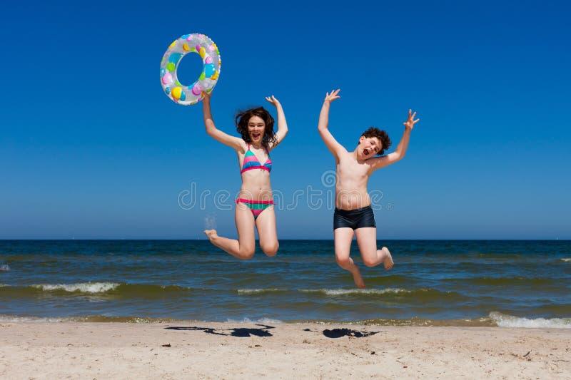 海滩跳的孩子 库存图片