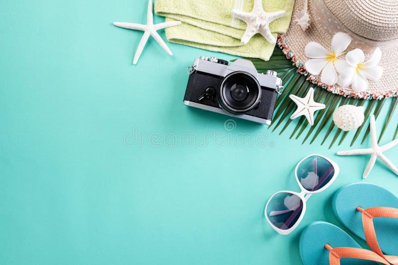 海滩辅助部件减速火箭的胶卷相机、太阳镜、触发器海星海滩帽子和海壳在绿色淡色背景为夏天 免版税库存图片