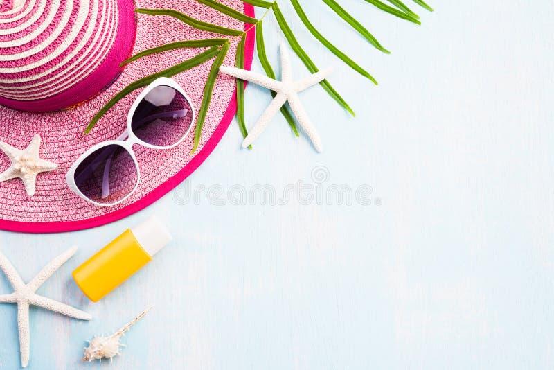 海滩辅助部件太阳镜、海星、海滩帽子和海壳在沙滩和蓝色木背景为夏天休假和 免版税库存照片