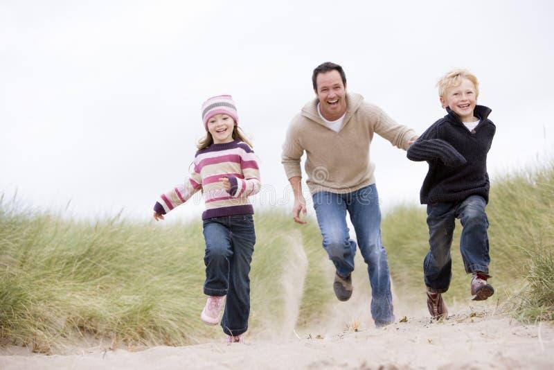 海滩运行二个年轻人的儿童父亲 免版税库存照片