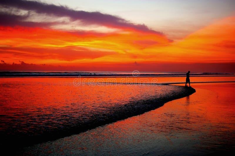 海滩遥远人日落走 免版税库存照片