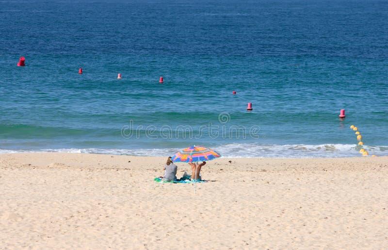 海滩遮阳伞含沙开会二下面妇女 免版税库存照片