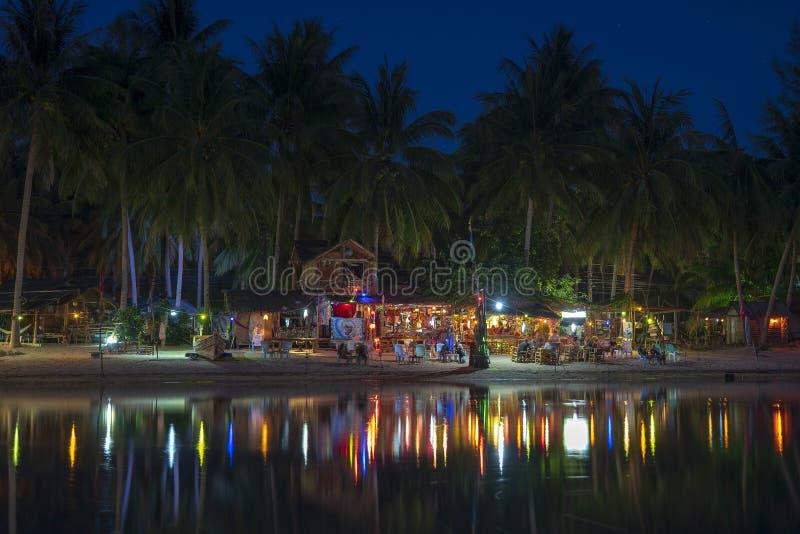 海滩酒吧、可可椰子树、海水和夜总会在热带海岛酸值阁帕岸岛,泰国的海水被反射 免版税库存照片