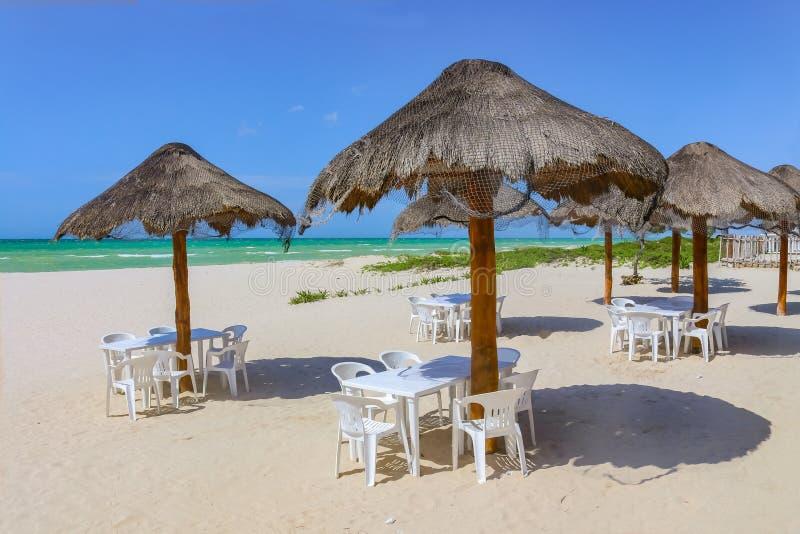 海滩酒吧- Tiki在沙滩的茅草屋顶伞与在底下白色塑料椅子和turquioise海和非常蓝天 免版税库存照片