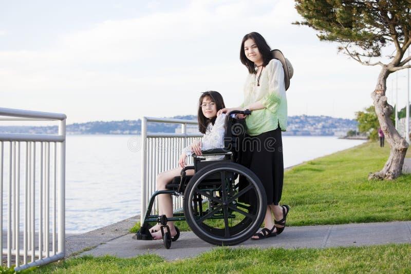 海滩采取轮椅的关心姐妹 库存图片