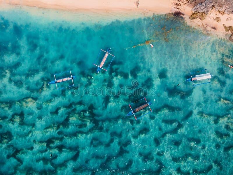 海滩顶视图与绿松石海水和传统亚洲小船,空中射击的 免版税库存照片