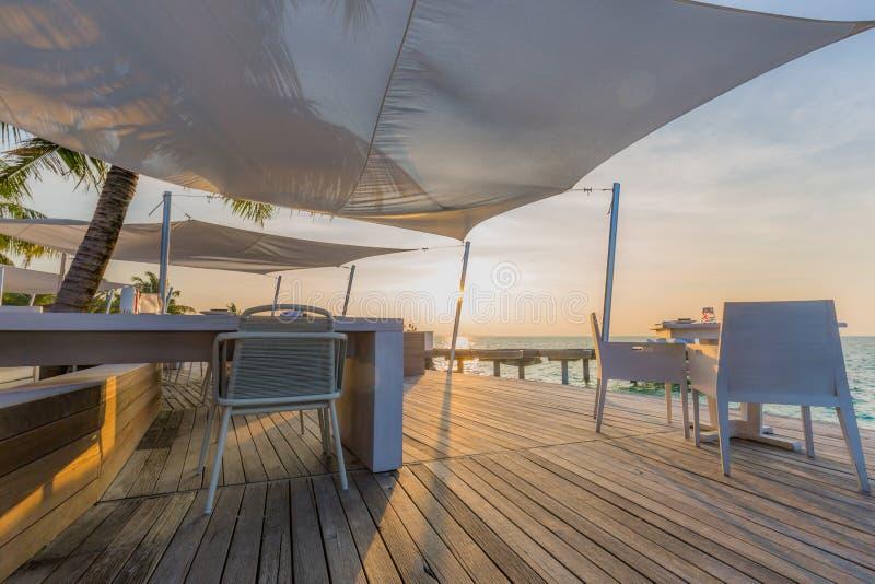海滩餐馆、日落光和软的颜色在木甲板有白色家具和海视图 库存图片