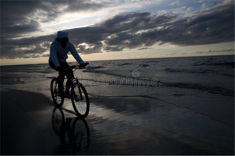 海滩骑自行车 免版税库存图片