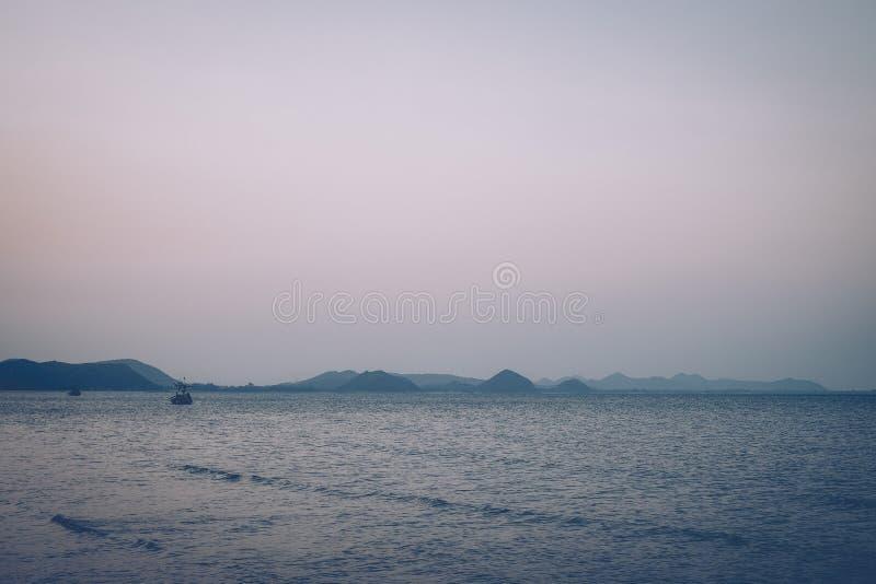 海滩,岩石,山 剧烈的金子和蓝色海岸线 锋利的粗砺的黑暗的石头装饰深蓝色宽海洋 免版税图库摄影