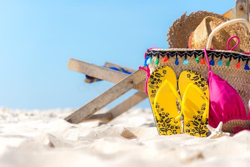 海滩formentera海岛妇女年轻人 比基尼泳装和啪嗒啪嗒的响声,帽子,鱼在沙滩的海滩睡椅附近担任主角并且请求反对蓝色海和天空背景, 免版税图库摄影