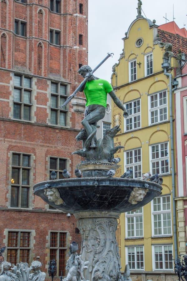 海王星在绿色T恤杉的` s雕象在买多市场街道在格但斯克老镇  库存图片
