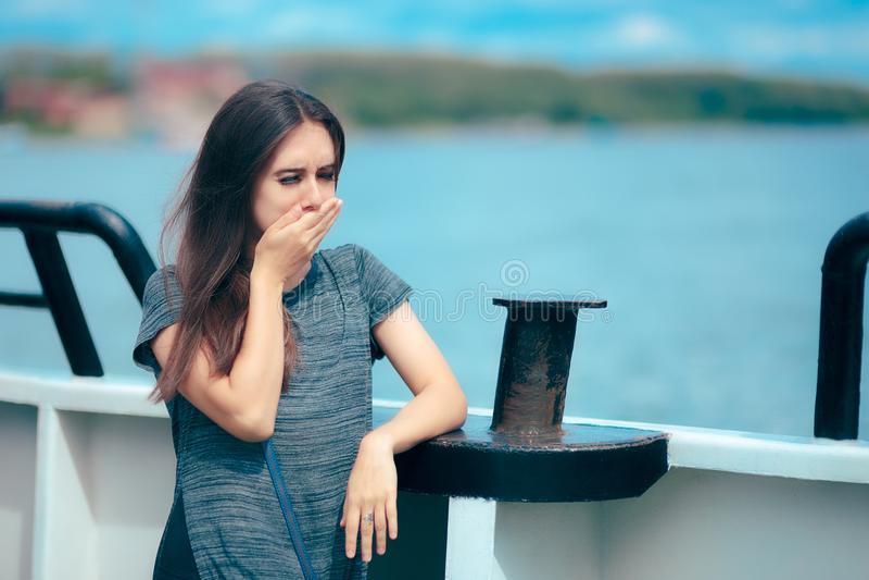 海病的妇女遭受的晕动病,当在小船时 免版税图库摄影