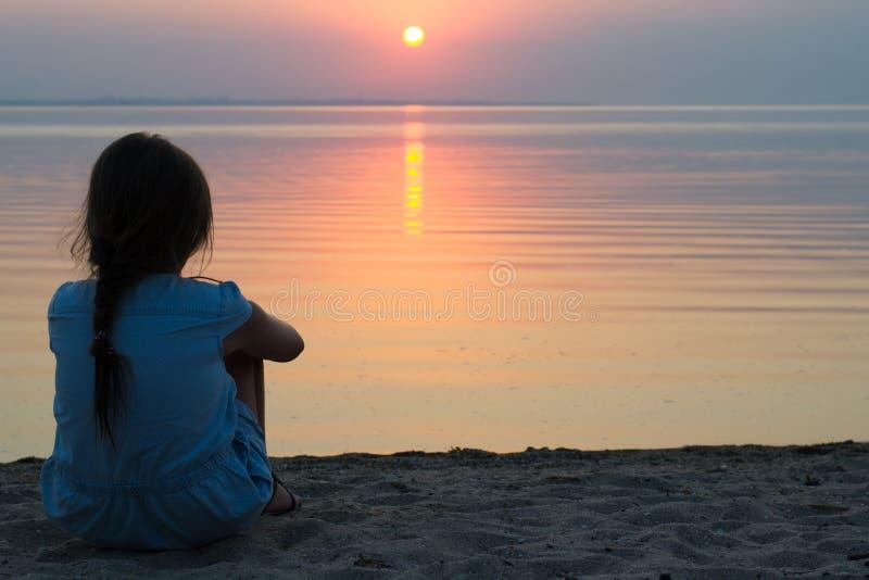 海的女孩日落的 库存照片